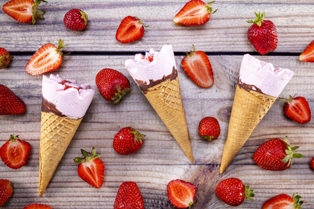Ice cream cones with strawberries on a vintage wooden table summer. Focus on ice cream.