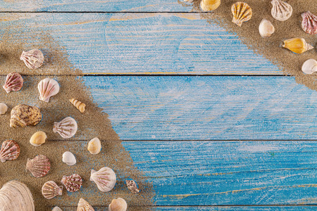 Summer time concept with sea shells on a blue wooden background and sand. Seashells frame on wooden background nautical border. Focus on seashells.