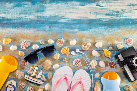 Beach accessories retro film camera sunglasses flip flop and sea shell on wooden. Top view of beach accessories on blue plank summer holiday banner travel concept. Focus on shells.