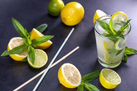 Cold refreshing summer lemonade with mint in a glass on a grey and black background. Focus on leaf in glass.