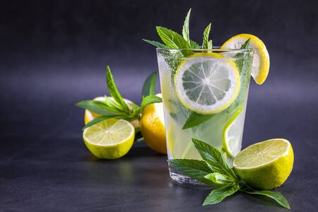 Cold refreshing summer lemonade with mint in a glass on a grey and black background. Focus on glass. Zdjęcie Seryjne