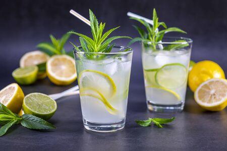 Limonade d'été rafraîchissante froide à la menthe dans un verre sur fond gris et noir. Concentrez-vous sur le verre.
