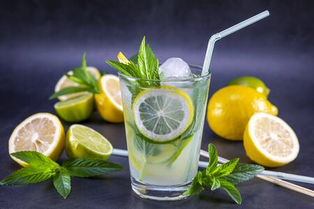 Cold refreshing summer lemonade with mint in a glass on a grey and black background. Focus on leaf and ice in glass.