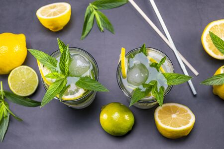 Top view of fresh lemonade with mint and ice in glasses on black background. Focus on leaf and ice.