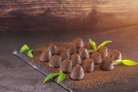 Homemade chocolate truffles with mint sprinkled with cocoa powder on slate. Focus on truffles