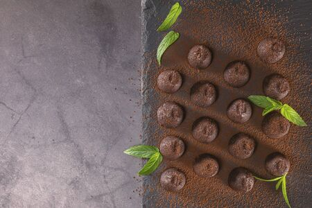 Top view of delicious chocolate truffles powdered with cocoa on slate.