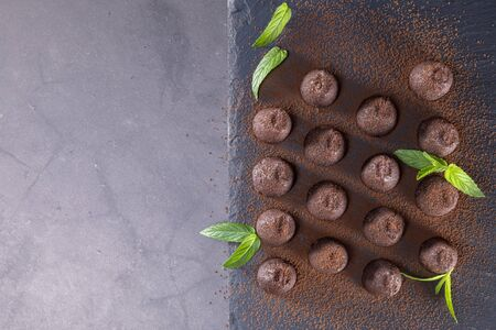 Top view of delicious chocolate truffles powdered with cocoa on slate. Focus on truffles. Archivio Fotografico