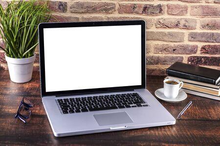 Laptop-Notizbuch mit leerem Bildschirm und Tasse Kaffee und Notizblockstift und Büchern auf Holztisch. Mock-up auf Holztisch mit Laptop mit leerem Bildschirm, Tasse Kaffee, Stift, Büchern und Blumen. Konzentrieren Sie sich auf die Tastatur. Standard-Bild