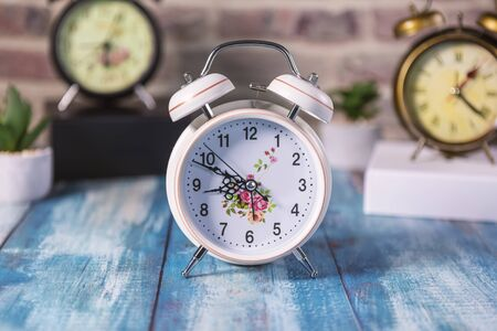Vintage background with retro alarm clock on table. Focus on first clock. Stockfoto