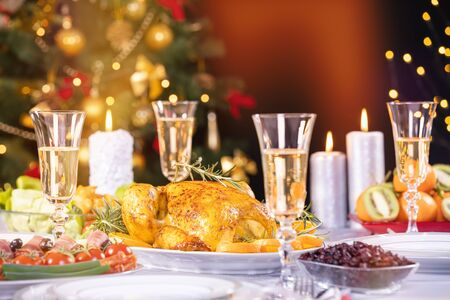 Christmas dinner. Chicken against glowing Christmas lights and burning candles. Holiday decorated table, Christmas tree, champagne and roasted turkey, Christmas served table. Focus on chicken! 版權商用圖片 - 131851129