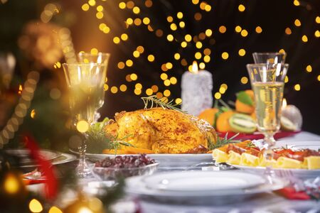 Christmas dinner. Closeup photo of tasty baked chicken against glowing Christmas lights and burning candles. Holiday decorated table, Christmas tree, champagne and roasted turkey, Christmas served table.