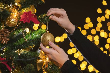 Girl decorates a Christmas tree. Closeup image of female hands decorating Christmas tree. 版權商用圖片 - 131851204