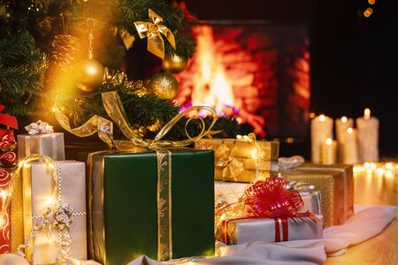 Stack of packed gift boxes under Christmas tree against burning fireplace. Lots of Christmas gifts under the tree. Candles on wooden floor. Focus on green box!