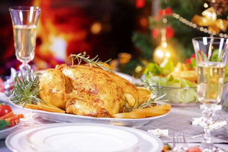 Christmas dinner. Chicken against glowing Christmas lights and burning candles. Holiday decorated table, Christmas tree, champagne and roasted turkey, Christmas served table. Focus on chicken!