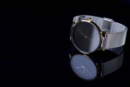 Black wrist watch for women with metal bracelet on glossy black background. 版權商用圖片