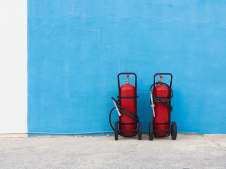 fire extinguishers: Two fire extinguishers in front of a blue painted wall Stock Photo