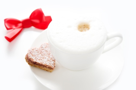 a cup of cappuccino with heart-shaped biscuits and a bow on a white background photo