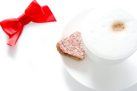 a cup of cappuccino with heart-shaped biscuits and a bow on a white background Stock Photo - 8807453
