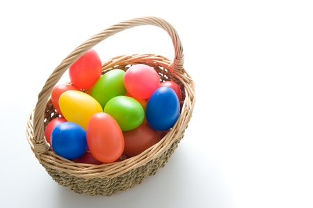 Basket with colorful Easter eggs on a white background photo