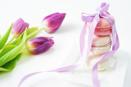 macaroon: Macaroons tied with purple ribbon on a white background with purple tulips