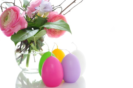 Bouquet of ranunculus with multicolor candles in the form of Easter eggs photo