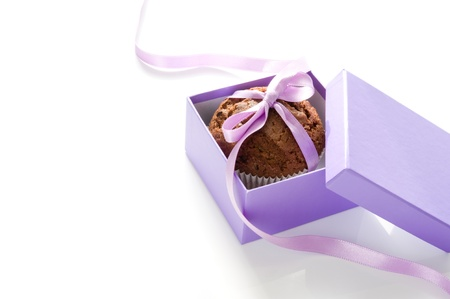 Chocolate muffin, tied with purple ribbon in a gift box on white background photo