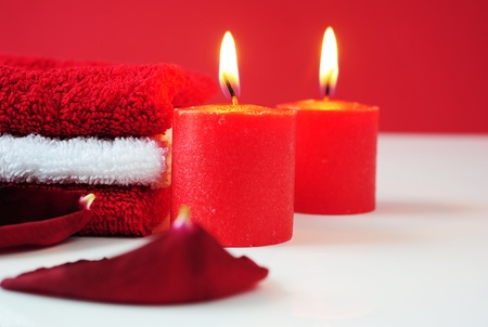 A tower of white and red towels, rose petals and lit red candles Stock Photo - 8994248