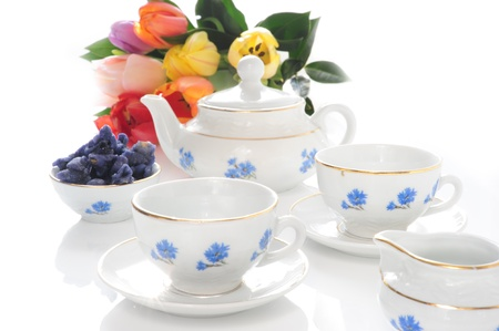 Tea Set with cornflowers, tulips and colorful candied violets in a bowl on a white background photo