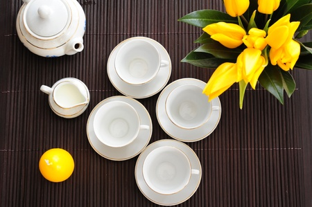 Tea set on a bamboo mat with yellow tulips and yellow candle in the form of eggs photo