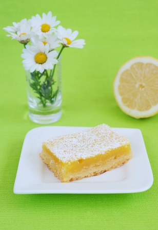 lemon cake on white plate with daisies and lemon with a green background photo