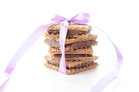 Square waffle with chocolate and nut filling, tied with purple ribbon on a white background photo