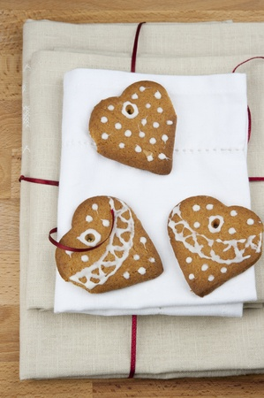 Honey cookies with heart-shaped, with ornaments on a pile of linen napkins tied with red ribbon on a wooden table photo
