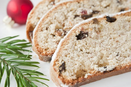 Pieces of Christmas Stolle on a white plate decorated with a sprig of fir tree and the ball photo