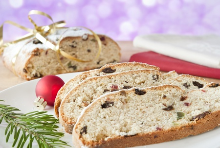 traditonal: Pieces of Christmas Stolle on a white plate decorated with a sprig of fir tree and the ball Stolle in the background, tied with gold ribbon and red and beige linen napkins