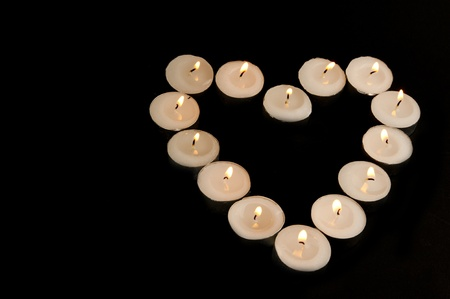 truelove: lighted candles on display in the shape of heart on a black background
