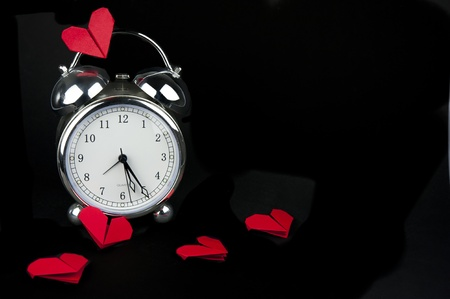 Silver vintage alarm clock with red hearts out of paper in the style of origami Stock Photo - 11764376