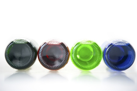 Four glass bottles, green, purple, red and purple bottoms lie ahead on a white background. photo