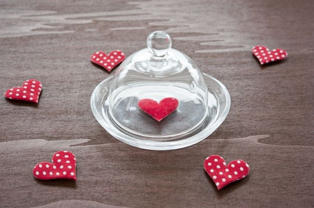 Hearts of red fabric with polka dots on a dark wooden table, a red sedvechko under a glass dome photo