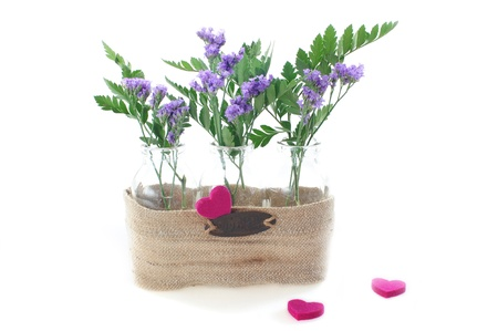 Purple Flowers In Three Glass Vases Connected By Sacking A Number