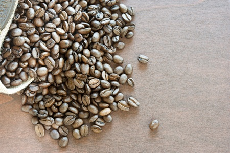 bag of roasted coffee beans on a dark wooden table, a horizontal frame photo
