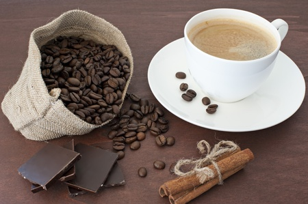 bag of coffee beans, pieces of dark chocolate, cinnamon sticks, tied with a rope, a white porcelain cup of freshly brewed coffee on a dark wooden background photo