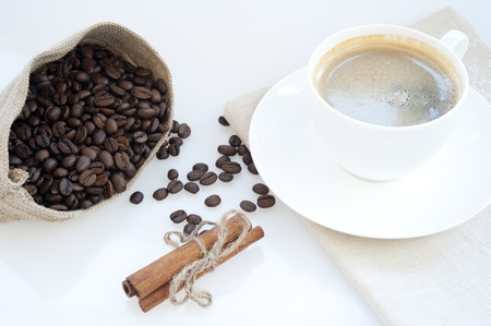 bag of coffee beans, cinnamon sticks, tied with a rope, a white porcelain cup of freshly brewed coffee on a white background photo