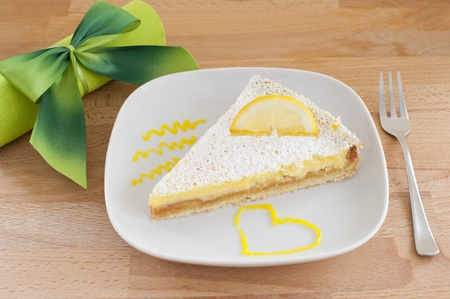 lemon cake on a white porcelain plate, dessert fork and a napkin tied with a bow green, wooden table photo