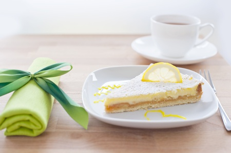 lemon cake on a white porcelain plate, dessert fork and a napkin tied with a bow green in the background with a cup of tea, wooden table photo