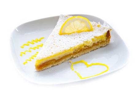 pie de limon: un pedazo de pastel de limón, adornado con una rodaja de limón en un plato blanco decorado con un corazón sobre un fondo blanco