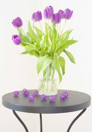 Bouquet of purple tulips in a glass vase on a black coffee table with purple decorative balls against a white wall