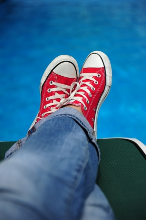 Legs in red sneakers on a background of blue water photo