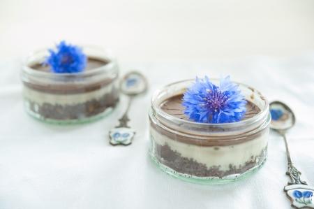 dois frascos de vidro com sobremesa de chocolate decorados com centureas duas colheres de linho guardanapo branco foto royalty free gravuras