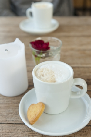 Cappuccino in a white cup and saucer with heart-shaped biscuits on a wooden table in the background and the rose candle photo