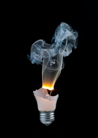 Broken light bulb burns and smoke from it on a black background photo